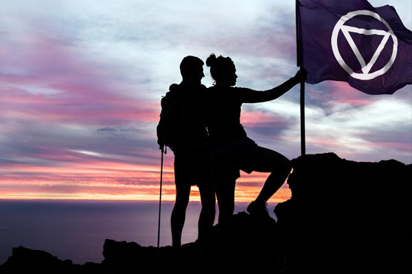 Two people raise the Audify Flag on top a mountain top as pioneers in hearing care